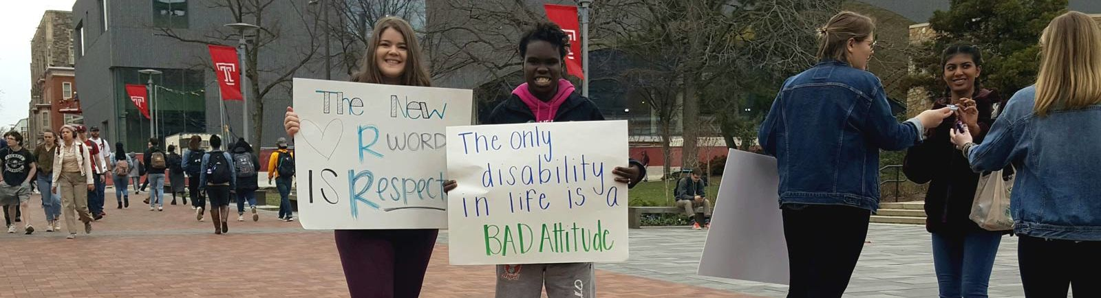 Temple students hold posters about the R-Word Campaign on campus at the bell tower