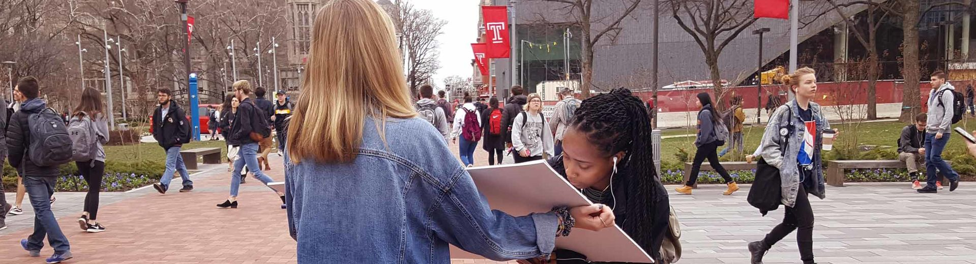 a student signs a poster held by another while others walk past